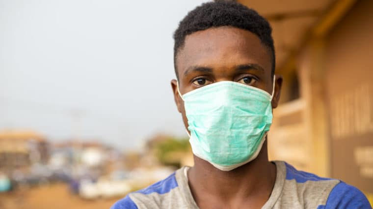 young handsome african man wore face mask preventing, prevent, prevented himself from the outbreak in his society.